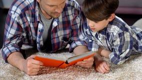 Skoncentrowany tata i syn czyta ciekawą encyklopedię dla chłopiec, edukacja zdjęcie royalty free
