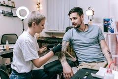 Skoncentrowany tatuażu artysta zakrywający w tatuażach robi podcieniowaniu obrazy royalty free