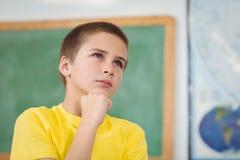 Skoncentrowany uczeń ma rękę na podbródku w sala lekcyjnej obrazy stock