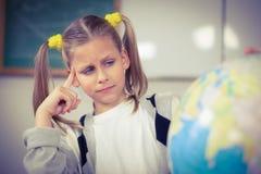 Skoncentrowany uczeń patrzeje kulę ziemską w sala lekcyjnej obraz stock