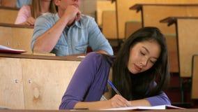 Skoncentrowany uczeń podczas lekcyjny ono uśmiecha się przy kamerą zbiory