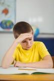 Skoncentrowany uczeń pracuje przy jego biurkiem w sala lekcyjnej fotografia stock