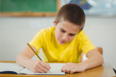 Skoncentrowany uczeń pracuje przy jego biurkiem w sala lekcyjnej zdjęcie stock