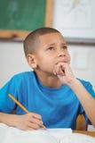 Skoncentrowany uczeń pracuje przy jego biurkiem w sala lekcyjnej zdjęcia stock