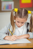 Skoncentrowany uczeń pracuje przy jej biurkiem w sala lekcyjnej obrazy stock
