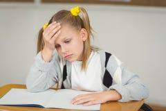 Skoncentrowany uczeń pracuje przy jej biurkiem w sala lekcyjnej obraz royalty free