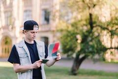 Skoncentrowany uczeń w nakrętce przy tłem uniwersytet czyta zadanie od jego notatnika zdjęcia stock