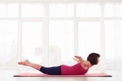 Skoncentrowany yogini praktyk ćwiczenia chyłu joga lub kobry poza obrazy stock