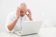 Skoncentrowany zmartwiony przypadkowy mężczyzna używa laptop przy biurkiem zdjęcia stock