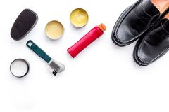 Skoomsorgprodukter Lädermanskor, skokräm, borstar, vax på vitt utrymme för kopia för bästa sikt för bakgrund royaltyfri foto