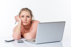 Skołowana nieszczęśliwa blond dziewczyna opiera na jej białym rzadkim biurku Obrazy Stock