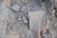 Skopaskyffel för sand som förläggas på en hög av sand som används för construc Arkivfoto