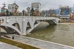 SKOPJE, DIE REPUBLIK MAZEDONIEN - 24. FEBRUAR 2018: Die Brücke von Zivilisationen und von Vardar-Fluss in der Stadt von Skopje Lizenzfreie Stockfotos
