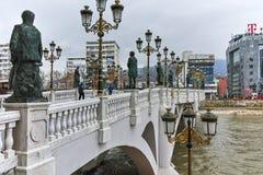 SKOPJE, DIE REPUBLIK MAZEDONIEN - 24. FEBRUAR 2018: Die Brücke von Zivilisationen und von Vardar-Fluss in der Stadt von Skopje Stockfoto