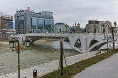 SKOPJE, DIE REPUBLIK MAZEDONIEN - 24. FEBRUAR 2018: Die Brücke von Zivilisationen und von Vardar-Fluss in der Stadt von Skopje Stockfotos