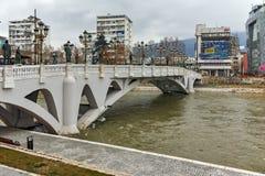 SKOPJE, DIE REPUBLIK MAZEDONIEN - 24. FEBRUAR 2018: Die Brücke von Zivilisationen und von Vardar-Fluss in der Stadt von Skopje Lizenzfreies Stockfoto