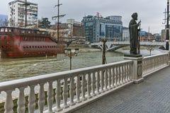 SKOPJE, DIE REPUBLIK MAZEDONIEN - 24. FEBRUAR 2018: Monument und Vardar-Fluss, der durch Stadt von Skopje-Mitte überschreitet Stockbilder