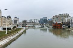 SKOPJE, DIE REPUBLIK MAZEDONIEN - 24. FEBRUAR 2018: Vardar-Fluss, der durch Stadt von Skopje-Mitte überschreitet Stockbild