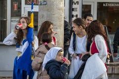 SKOPJE, MACEDÔNIA - 24 DE OUTUBRO DE 2015: Grupo bosniano da dança popular de meninas que bebem Coca Cola após um desempenho do f Fotografia de Stock