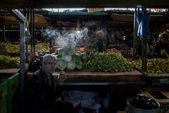 SKOPJE, MACEDONIË - OKTOBER 24, 2015: Mensen verkopende kolen en peper die op Skopje-markt een sigaret roken bij schemer Royalty-vrije Stock Afbeeldingen