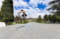 Low view of skillful cyclist jumping high up against sky. Skopje, Macedonia - circa Apr, 2013: Below view of skillful cyclist jumping high up against sky Royalty Free Stock Image
