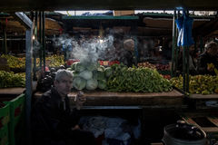 SKOPJE, MACEDONIA - OCTOBER 24, 2015: Man selling cabbages and peppers on Skopje market smoking a cigarette at dusk Royalty Free Stock Images