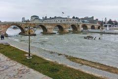 SKOPJE, A REPÚBLICA DA MACEDÔNIA - 24 DE FEVEREIRO DE 2018: Centro da cidade de Skopje, ponte de pedra velha e rio de Vardar, Fotografia de Stock