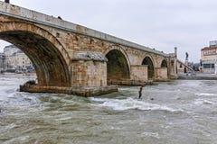 SKOPJE, A REPÚBLICA DA MACEDÔNIA - 24 DE FEVEREIRO DE 2018: Centro da cidade de Skopje, ponte de pedra velha e rio de Vardar, Fotografia de Stock Royalty Free