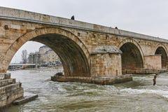 SKOPJE, A REPÚBLICA DA MACEDÔNIA - 24 DE FEVEREIRO DE 2018: Centro da cidade de Skopje, ponte de pedra velha e rio de Vardar, Fotos de Stock