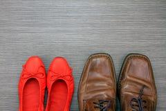 Skor av en man och en kvinna på golvet, modetillbehör Arkivfoton