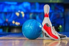 Skor, bowlingstift och boll för att bowla leken Arkivbilder