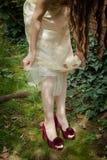 Skor den unga kvinnan för closeupen i elegant silkeslen kjol och hög häl s Royaltyfri Foto
