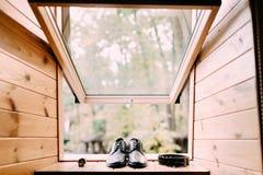 Skor för brudgum` s, läderbälte och klocka på ljus träfönsterbrädabakgrund Uppsättning för man` s Royaltyfri Foto