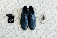 Skor för brudgum` s och cufflinks, ett armbandsur på en ljus bakgrund gifta sig för trappa för stående för brudbegreppsklänning K Fotografering för Bildbyråer