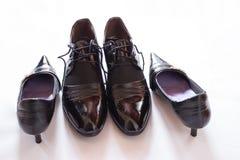 Skor för flicka` s och patenterade skor för man` s Royaltyfri Foto