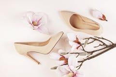 Skor för höga häl för nakenstudie kulöra och magnoliablommor arkivbilder