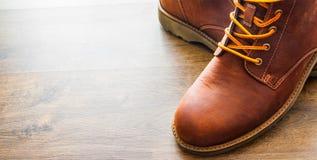 Skor för läderkängor på den bruna trätabellbakgrunden Med kopiera utrymme Arkivbild
