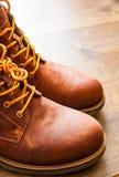 Skor för läderkängor på den bruna trätabellbakgrunden Med kopiera utrymme Royaltyfri Foto