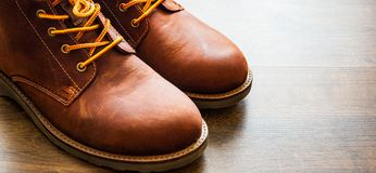 Skor för läderkängor på den bruna trätabellbakgrunden Med kopiera utrymme Royaltyfria Foton