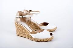 Skor för sandaler för ` s för vita kvinnor på en vit bakgrund Arkivfoton
