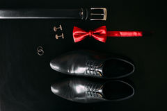 Skor för svart man` s, cufflinks, vigselringar, ett svart bälte och a Arkivbilder