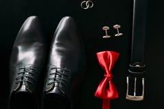 Skor för svart man` s, cufflinks, vigselringar, ett svart bälte och a Royaltyfria Bilder