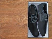 Skor för svart man` s i asken på trägolvet Arkivfoton
