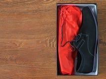Skor för svart man` s i färgrikt förpacka på ett trägolv Arkivfoton