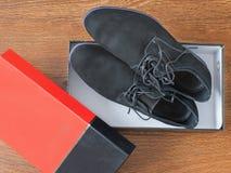 Skor för svart man` s i originalet som förpackar på ett trägolv Arkivbilder