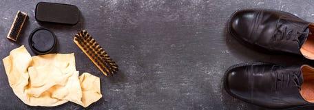 Skor för svart man` s med omsorgtillbehör Arkivfoto