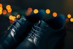 Skor för svart man` s med snör åt Mot bakgrundsbokeh Arkivfoto