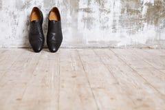 Skor för svart man` s mot en vägg i retro inre Arkivbild