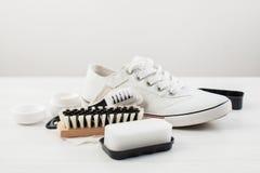 Skor för vit för omsorgsko- och kvinna` s på vit Arkivfoton