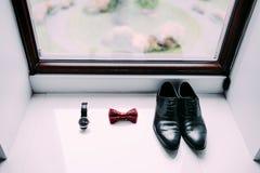 Skor, fluga och klocka för brudgum` s på ljus fönsterbakgrund Royaltyfri Fotografi